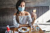 Young woman wearing surgical face mask, eating dessert, using mobile phone and spending time in the cafe during epidemic