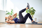Fit woman doing abs exercises at home to strengthen core muscles