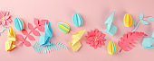 Easter holiday creative background with papercraft eggs, flowers, origami bunny on coral pink background, trendy paper craft holiday springtime background, banner