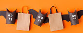 Autumn season Halloween holiday sale concept - toy from toilet roll tube, recycle idea and paper craft shopping bag on orange background, eco-friendly easy diy, flyer, coupon