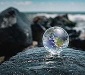 Crystal ball reflecting globe of the earth in beach