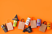Happy halloween holiday concept. Halloween decorations, pumpkins, bats, witch, ghosts on orange background. Halloween party greeting card mockup with copy space. Flat lay, top view, overhead