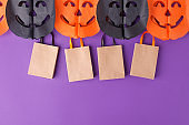 Halloween paper garland with black orange pumpkin jack-o-lantern and shopping pack hanging on the purple wall. Easy crafts for kids. Copy space, October holiday banner, festive party idea