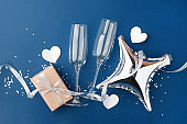 wineglasses and gift box on classic blue background. Background for holiday, birthday, wedding, Valentine's day, Women's Day party. Top view, flat lay composition. Copy space