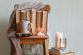 Self isolation, stay home, hygge and cozy home concept - books, cup of coffee or hot chocolate and candles, seasonal autumn fall winter relax time, concept of read, monochrome, banner