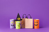Autumn season Halloween holiday sale concept - toy from toilet roll tube, recycle idea and paper craft shopping bag on purple background, eco-friendly easy diy, flyer, coupon