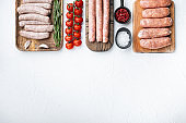 Set of raw pork, beef and chicken sausages, flat lay with space for text, on white background