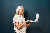 Cheerful mature old woman using laptop computer.