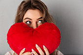 Close-up image of woman in t-shirt hiding behind joy heart