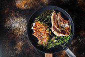 Grilled organic  pork steak with herbs on bone  in grill frying pan hot with smoke and hot oil just from fire, top view cooking bone with seasonings rustic metal background