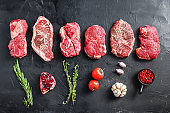 Raw set of rump, top blade, chuck roll beef steak cut, with rosemary, garlic, pomgranate, tomatoe, peppercorns on black textured background, top view.