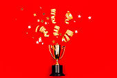 Golden winners cup with confetti