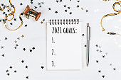 Holiday decorations and notebook with new year resolutions list