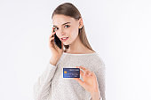 Beautiful working woman with smart business look is showing her credit card. Office worker with casual look. Beautiful office worker.