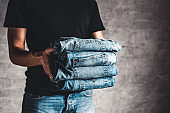 close up stack of folded denim blue jeans in hand over gray wall background