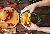 Female hands holds a burger with chicken, fried egg and cheese on a rustic wooden background