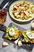 Fresh Caesar salad with poached eggs and avocado on toast on concrete background.