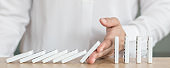 Business solution strategy stoping domino effect concept for financial or investment protection and successful intervention with corporate person's hand blocking the collapse disruption.
