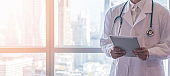 Telemedicine by medical doctor or physician consulting patient's health telehealth online using mobile tablet in clinic or hospital for professional digital emergency healthcare assistance service