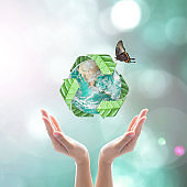 World environment day and ecology concept with woman human hands under green planet with recycle sign. Elements of this image furnished by NASA
