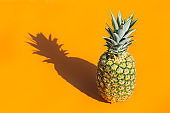Pineapple with trendy hard light and shadows orange background
