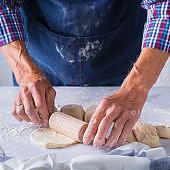 Baking at home concept. Senior man hands cooking, making dough