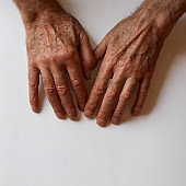 Mature adult men hands against white background top view. Human body part