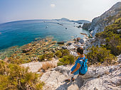 Young woman with backpack standing on a cliff in front of the ocean. Ponza Island coast, Italy.