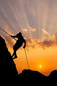 Climber on sunset sky background