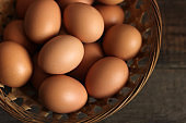 Eggs in a basket on a wooden background.