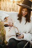 Hipster woman pouring hot coffee in glass cup on background of rural herbs in sunset. Alternative coffee brewing outdoors in sunny light. Atmospheric rustic moment. Wanderlust