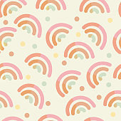 Cute pink rainbow in pastel colors and colorful dots, seamless pattern. Modern hand drawn vector in cartoon style. Baby nursery room in scandinavian style. Wrapping paper or kids textile concept