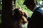 amazing sensual boho bride and stylish elegant groom, gentle touch in sunny woods