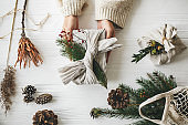 Hands holding stylish christmas gift wrapped in linen fabric with green fir branch and red berries on rustic white table with pine cones, flat lay. Zero waste Christmas, plastic free holidays