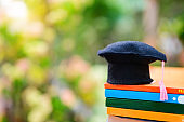 Education concept : Graduation hat or Mortarboard put on many book with background natural background.