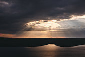 Beautiful view of sun rays from dark clouds above lake. Sunset light over hill and river landscape. Dramatic moody scenery. Bakota lake and Dniester river in Ukraine
