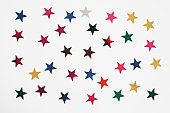 Colorful stars confetti or glitter on white background, isolated. Stylish atmospheric image. Happy birthday concept. Holiday decorations. Magic and Christmas. Party backdrop