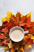 Autumn mood composition. Cup of coffee with maple leaves on white background. Flat lay, top view, copy space.
