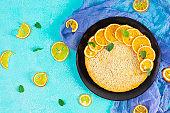 Delicious homemade orange tart on blue background