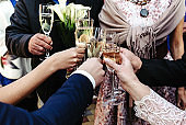 hands of happy people toasting and cheering with glasses of champagne, celebrating wedding, luxury life concept