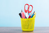Colorful pens and orange scissors are in the green plastic basket and put on wooden table isolated on blue pastel background.