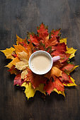 Cup of coffee with maple leaves on dark wooden background. Autumn mood flat lay, family celebration, thanksgiving day, home weekend