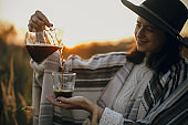 Alternative coffee brewing in travel. Hipster woman in hat pouring fresh hot coffee in glass cup on background of sunny warm light in rural herbs. Atmospheric rustic tranquil moment