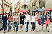 many confident young happy women walking having fun on background of old european city street, celebrating friendship concept, moments of happiness