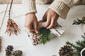 Hands decorating stylish christmas gift in linen fabric with red berries branch on background of white rustic table with pine cones and green fir. Florist preparing zero waste Christmas gift.