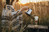 Alternative coffee brewing outdoors in travel. Hipster woman pouring hot water in filter with coffee in glass flask on background of sunny warm light in rural herbs. Back view. Authentic moment