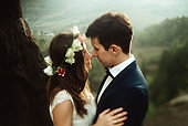 luxury happy bride and stylish groom hugging each other with tender on background of  sunny rocks in amazing mountains