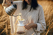 Hipster woman pouring hot water from steel kettle in glass flask dripper with filter on background of rural herbs in sunset. Alternative coffee brewing. Atmospheric rustic moment