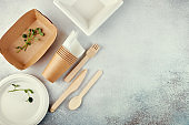 Biodegradable disposable tableware. Paper plates, cups, boxes. Wooden cutlery. Flat lay