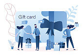 Gift card and promotion strategy. Handsome man gives woman plastic gift voucher.